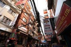 Nepalileute, die morgens hinunter die Thamel-Straße unter Sonnenaufgang in Kathmandu gehen Lizenzfreies Stockfoto
