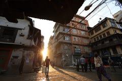 Nepalileute, die morgens hinunter die Thamel-Straße unter Sonnenaufgang in Kathmandu gehen Lizenzfreie Stockbilder