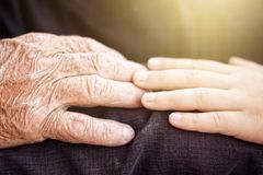 Nephew touching grandfather's hand in sunlight Royalty Free Stock Image