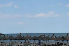 Neptun, Румыния - 8-ое июля 2017: зонтики пляжа - и холодный бурный день на пляже в румынском взморье в Neptun, Constanta, r Стоковые Изображения
