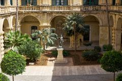 Neptune Courtyard in the Grandmaster`s Palace. Valletta. Malta. The view of Neptune Courtyard with statue of Neptun and a garden landscape in the middle Royalty Free Stock Photo