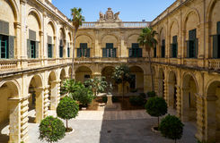 Neptune Courtyard in the Grandmaster`s Palace. Valletta. Malta. The view of Neptune Courtyard with statue of Neptun and a garden landscape in the middle Royalty Free Stock Photos