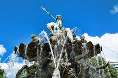 Neptune fountain in Berlin  with jets of water on blue sky background Royalty Free Stock Photos