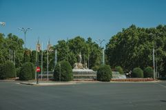 Neptune fountain among leafy trees in Madrid. Charming Neptune fountain among leafy trees on the Del Prado walkway, in a sunny day at Madrid. Capital of Spain royalty free stock photos