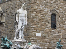 The Neptune fountain and Palazzo Vecchio in Florence, Italy . Detail of the Neptune statue.  Stock Photos