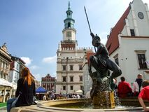 Neptune fountaine located in old market in Poznan in Poland. Neptune fountaine in Poznań with tourists gathered around it. City hall buiding and old town in Royalty Free Stock Photography