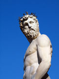 Neptune - greek god statue. Statue of the Roman God Neptune in the Piazza della signoria in Florence.  Marble sculpture against blue sky background Stock Photo