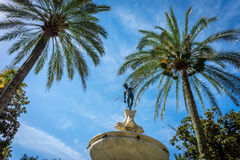Neptune under the palm tree in Alcazar garden with a blue sky in. Neptune under the palm tree in Alcazar garden on a summer day with a blue sky in Seville Royalty Free Stock Photography