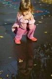 ner flicka som little near pölregn sitter Royaltyfria Foton