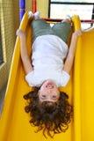 ner flicka som little skrattar glidbanaöversidan Royaltyfri Fotografi