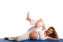 ner liggande övande gravid kvinnayoga Arkivfoto