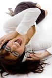 ner lycklig lyssnande liggande musik till kvinnan Fotografering för Bildbyråer