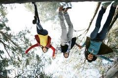 ner vänner som hoppar översidan Arkivbild