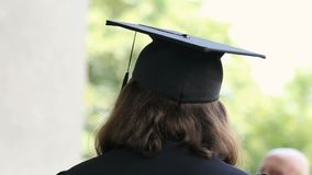 Nerd in academic dress ready to receive diploma of higher education, back view. Stock footage stock video