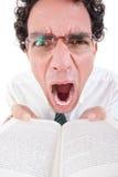 Nerd arrabbiato in camicia e legame con i vetri che tengono libro aperto Immagini Stock Libere da Diritti