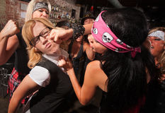 Nerd Attacked By Gang. Female nerd with eyeglasses punched in fight with gang Royalty Free Stock Images