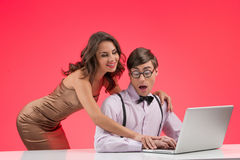 Nerd and beautiful girl. Shocked nerd man working at the compute royalty free stock image