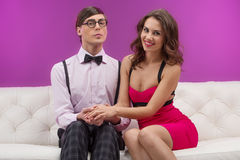 Nerd and beauty. Confident nerd men sitting on the couch near beautiful young women and holding her hand Royalty Free Stock Photo