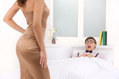 Nerd and beauty. Scared nerd men lying on the bed and looking at beautiful women in dress royalty free stock photography