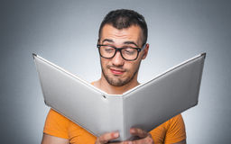 Nerd with book. Funny man reading book - holding folder against dark gray background. Close up of nerd Stock Image