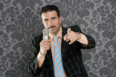 Nerd businessman microphone leader point finger. Retro mustache singer man tacky suit on vintage wallpaper background Royalty Free Stock Photo