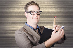 Nerd Businessman minuting massive business plan. Funny nerd businessman minuting massive business plan when writing with huge pencil in black note book. Wood Stock Photo