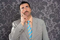 Nerd businessman pensive gesture silly funny retro. Mustache retro salesman with vintage suit and pensive gesture in wallpaper Royalty Free Stock Images