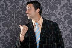 Nerd businessman portrait pointing thumb finger. Salesperson portrait pointing with thumb finger on wallpaper background Stock Photo