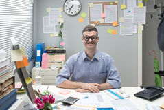 Nerd businessman at work. Funny nerd businessman at desk with thick glasses smiling at camera Royalty Free Stock Photos