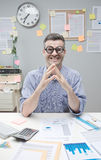 Nerd businessman at work. Funny nerd businessman at desk with thick glasses smiling at camera Stock Photo