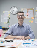 Nerd businessman at work. Funny nerd businessman at desk with thick glasses smiling at camera Stock Photos