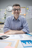 Nerd businessman at work. Funny nerd businessman at desk with thick glasses smiling at camera Stock Photography