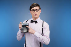 Nerd with calculator. Young nerd man holding calculator and pointing it while isolated on blue stock image