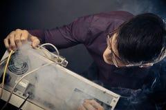 Nerd con fumo che esce dal suo pc fotografie stock