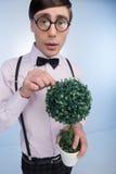 Nerd con la pianta. Giovane pianta della tenuta dell'uomo del nerd in sue mani mentre fotografie stock