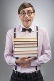 Nerd con la pila di libro. Giovane uomo del nerd che tiene una pila di libro mentre Fotografia Stock