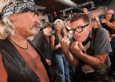 Nerd Confronting Gang Member. Nerd confronting tough gang member in leather vest in bar Stock Photos