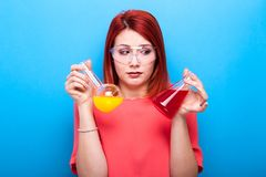 Nerd confused scientist woman wearing protective glasses and hol. Ds two tubes with colored liquid in her hands on blue background Royalty Free Stock Images