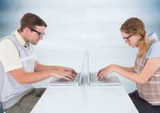 Nerd couple at laptops against blurry blue wood panel. Digital composite of Nerd couple at laptops against blurry blue wood panel Royalty Free Stock Images