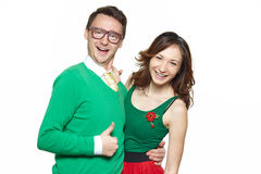 Nerd couple showing thumbs up. Interracial weird nerd couple showing OK sign. Caucasian young men wearing eyeglasses and smiling asian women showing thumbs up Royalty Free Stock Photography