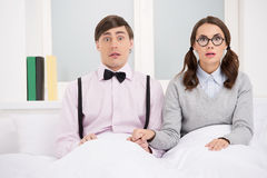 Nerd couple. Surprised nerd couple sitting on the bed and lookin Stock Image