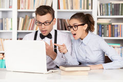 Nerd couple. Surprised young nerd couple in glasses looking at computer monitor and keeping mouth open while sitting together at the library royalty free stock photos