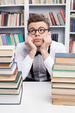 Nerd dreaming. Bored young man in shirt and bow tie sitting at the table in library and holding head in hands while two book stacks laying on the foreground Stock Images
