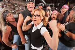 Nerd Flexing with Gang. Cute female nerd flexing muscles with gang of bikers Royalty Free Stock Photography