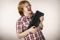 Gamer man holding computer keyboard Royalty Free Stock Images