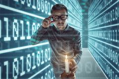 Nerd gets lost in cyberspace. Computer Nerd with glasses and a candle in one hand is walking through a maze with walls made out of binary code Royalty Free Stock Photo