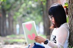 Nerd Girl Reading the Book of Loving Heart.  stock images