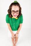 Nerd girl shrugging shoulder portraying shyness. Studio shot Royalty Free Stock Image