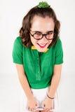 Nerd girl shrugging shoulder portraying shyness . Studio shot Stock Image