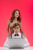 Nerd with girlfriend. Confident nerd man working at the computer Stock Photo